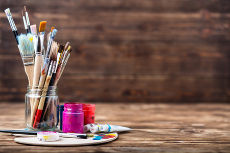 Artists workshop. Canvas, paint, brushes, palette knife lying on the table.Art tools.Artist workplace background.Acrylic paint and brushes.Art picture with copy space and for add text.