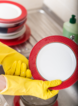 Cleaning dishware kitchen sink sponge washing dish. Close up of female hands in yellow protective protective gloves washing