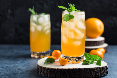 Fresh summer cocktail with orange juice and ice cubes. Glass of orange soda drink on dark background