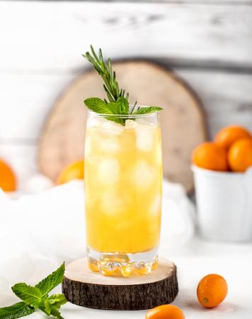 Fresh summer cocktail with orange juice and ice cubes. Glass of orange soda drink on white background Stock Photo