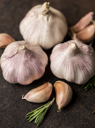 Fresh garlic with chili pepper and rosemary on wooden background. Garlic bulbs Stock Photo