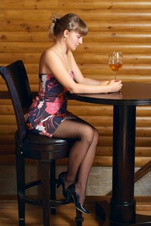 mujeres sentadas: Mujer hermosa joven sentado en la cafeter�a con un vaso de vino Foto de archivo