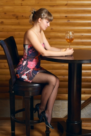woman drinking wine: Young beautiful woman sitting in the cafe with a glass of wine