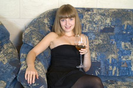 Young beautiful woman sitting on a sofa with glass of wine photo