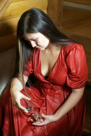 Sorrowful asian woman in the red dress sitting on the stairs with the glass of wine photo