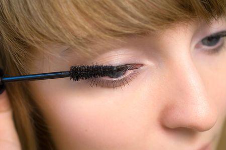 Young woman applying mascara to her eyelash
