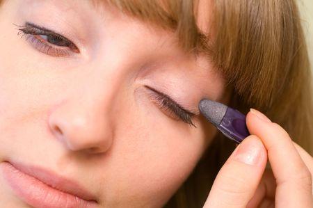 Young woman applying eyeshadow to her eyes photo