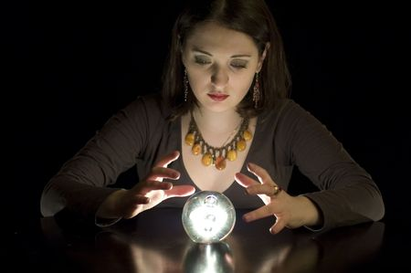 clairvoyance: Woman fortuneteller with crystal ball in darkness