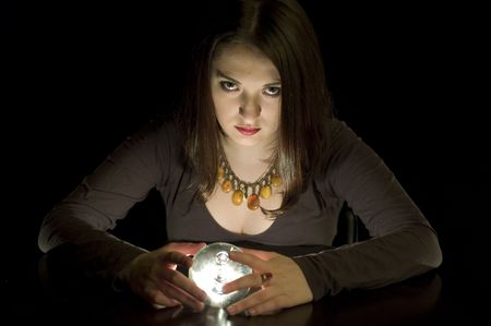 Woman fortuneteller with crystal ball in darkness photo