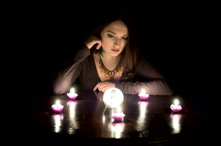 Woman fortuneteller with crystal ball in darkness