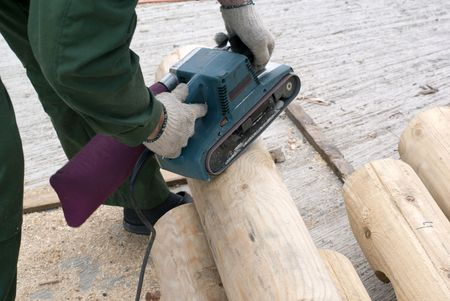 Carpenter smoothing the log on the construction Stock Photo - 7734573