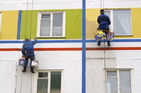 fachada: House painters paint the facade of building
