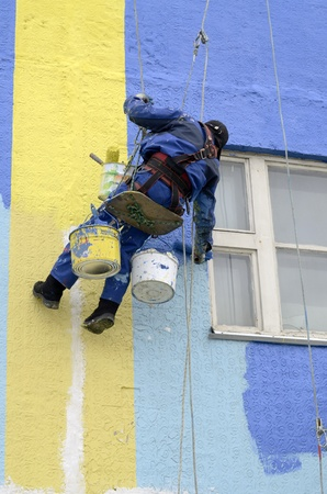 House painters paint the facade of building photo
