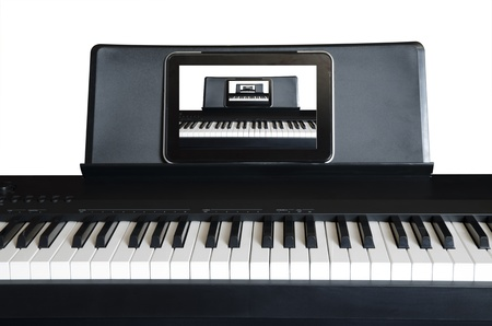 Electric piano with tablet PC on the holder and diminishing picture  photo