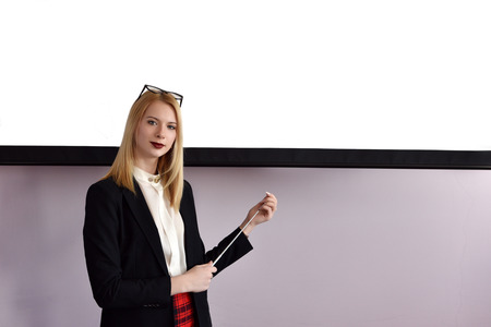 teaching adult: Young beautiful woman with pointer standing against the blank screen
