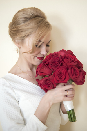 Young beautiful bride with the bouquet of red roses