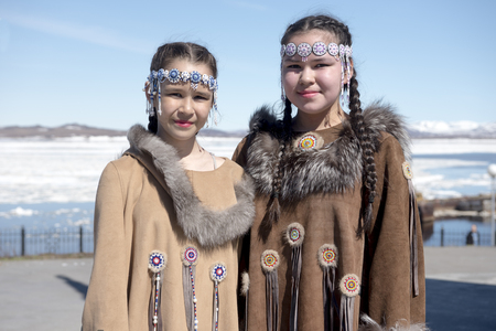 Two chukchi girls in folk dress against the Arctic landscape Stock fotó
