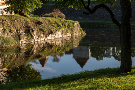 Reflection of old castle in the moat lit with low sun in the evening