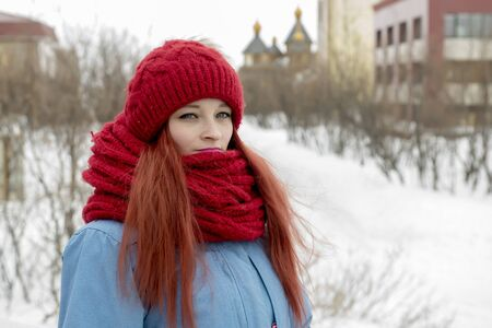 Portrait of young beautiful woman in red hat and red comforter Фото со стока