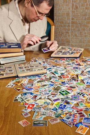 sello postal: Filatelista est� examinando un sello antiguo con lupa Editorial