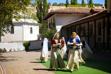 Bakhchisarai, Ukraine - May 2, 2013: Female folklore group from Crimea performs traditional dance of crimea tatars in inner courtyard of Khan Palace (Hansarai)