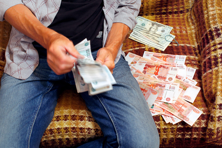 counts: Man counts russian rubles sitting on sofa