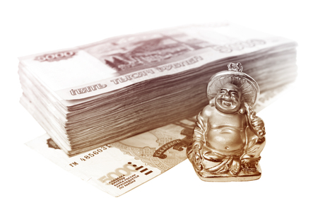 smiling buddha: Small statuette of smiling buddha bringing luck and stack of fivethousand bills of russian rubles isolated on white Stock Photo