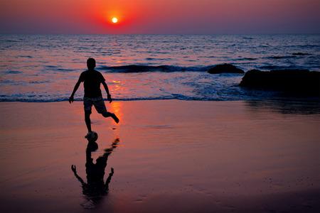 plays: Teenager plays football at sunset