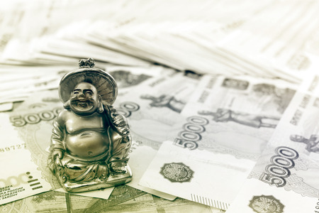 smiling buddha: Small statuette of smiling Buddha and russian rubles