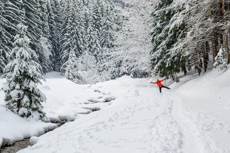 Young girl in red doing a funny pose, while on a hiking trail, in Winter, near a river, with fresh snow around and fir trees - late March in Piatra Mare (Carpathian) mountains, Romania