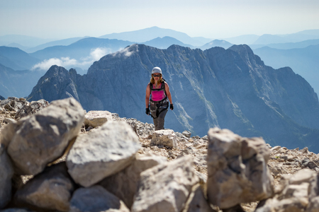Female climber finishing a via ferrata route on Veliki Mangart (Mangrt) peak, in the Julian Alps, Triglav National Park, located at the border between Slovenia and Italy, on a bright, hot, Summer day. 免版税图像
