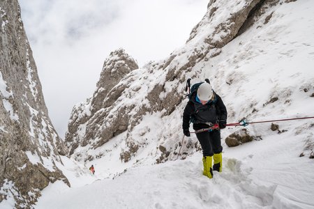 Female alpinist rappeling into a steep canyon filled with snow, during a Winter hiking trip, in Piatra Craiului mountains, part of the Carpathian mountains, in Romania.