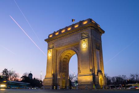 Triumphbogen (Arcul de Triumf) in Bukarest, Rumänien, bei Sonnenuntergang, mit blauem und rosa Himmel. Dieses triumphale Denkmal in der Kiseleff Road befindet sich in einem niedrigen Winkel und mit langer Belichtungszeit. Standard-Bild