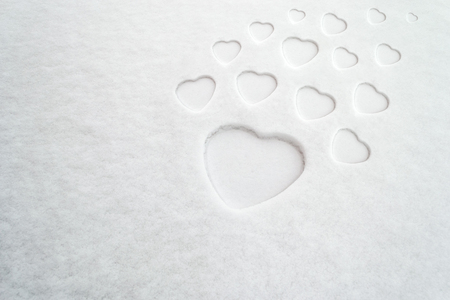 Pattern of white hearts of different sizes on fresh powder snow, with space for text. Concept for: mothers day, peace, purity, positive impact, love, romance, family, diversity, expansion. Фото со стока