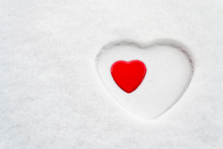 Big white heart outline in snow with a smaller red heart placed inside. Concept for: love, acceptance, motherhood, mother's day, women's day, peace, romance.