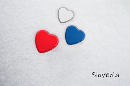 Colors of the slovenian flag (Red (Pigment), Medium Persian Blue, White) painted on three hearts. Snow background with the country, Slovenia, written on bottom right. Concept for tourism.