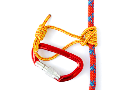 Klemheist or French Machard knot with a red locked carabiner attached. Can be tied with webbing or cord and is uni-directional, meaning it can only be loaded by a pull from one direction. Stock Photo