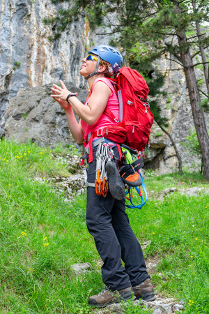 Happy climber girl with a red backpack, quickdraws, climbing shoes, chalk bag attached to her harness, making a wish for succeeding on a sport climbing route, while looking up at the stone wall. Banque d'images
