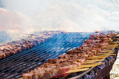 Chicken and lamb skewers on a simple, rustic grill laid out on the sand of a greek island. Close up of smocking meat being cooked.