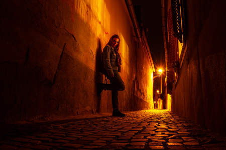Moody portrait of a young woman on a narrow urban passage, at night, next to open window shutters, in Sibiu (Hermannstadt), with scarce street lights reflecting yellow/orange rays on the cobbles.