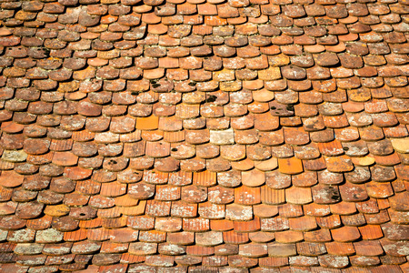 Abstract pattern of old, traditional, brown/orange, ceramic, overlapping shingles (tiles, schindle/schindel in German) on a house roof, lit in the morning sun light, in Sibiu, Transylvania, Romania.