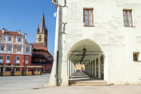 Old, medieval, white building with a corridor with several archways and a church tower in the background, on 'Piata Mica' Square - Sibiu (Hermannstadt), Transylvania, Romania