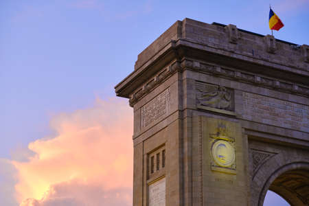 A corner of the Arch of Triumph in Bucharest, Romania, during a sunset with pink and orange clouds. Main touristic landmark, sightseeing spot. Zdjęcie Seryjne