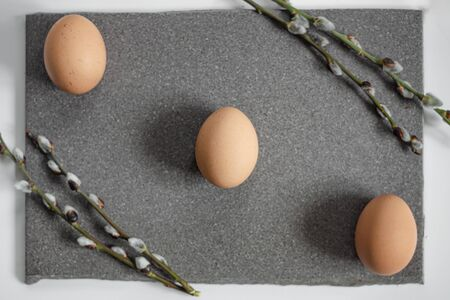 Three beige eggs lie on the granite surface, willow twigs in the corners. Banco de Imagens