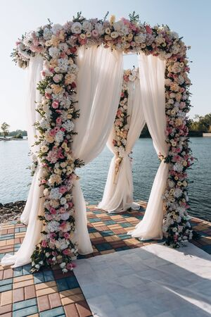 Beautiful wedding set up. Area of the wedding ceremony. Round arch, white chairs decorated with flowers, greenery. Cute, trendy rustic decor. Part of the festive decor, floral arrangement. 免版税图像