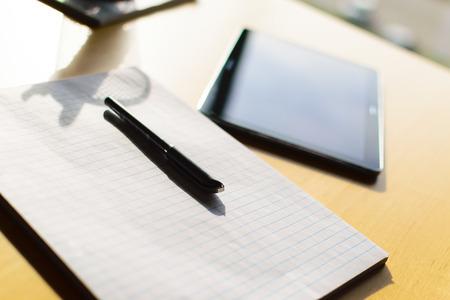 pluma y papel: pluma, papel y la tableta sobre la mesa en gran wiindow. Las sombras que caen del l�piz bote