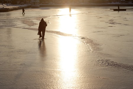 Silhouette of the fisherman on thin to ice of the river photo