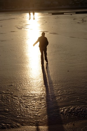 Silhouette of the girl on thin to ice of the river