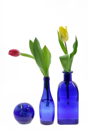 Fresh tulips in beautiful dark blue vase and a sphere photo