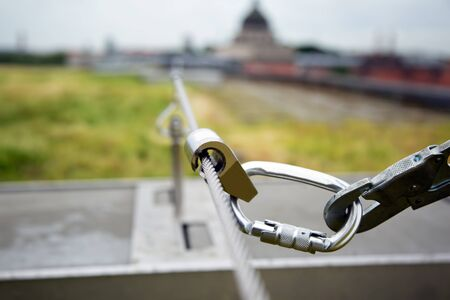 Close-up of a runner of a safety carabiner on a rope against the background of the city